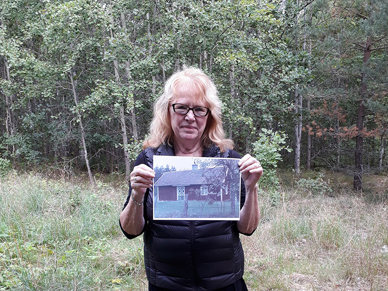 Traveler hold a photo of the cottage her ancestor lived in before he emigrated. She stand on the land where the cottage where.